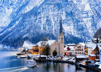Hallstatt near Salzburg, in Austria, Europe. Winter in Salzkammergut. Travel to Austrian city with lake at Christmas. Alpine Land with snow. View on Village near Alps mountains with beautiful Church.
